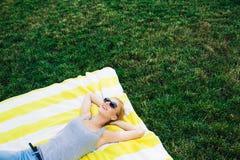 Chica joven feliz que descansa sobre césped Fotografía de archivo