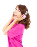 Chica joven feliz que escucha y que sostiene el auricular Fotos de archivo