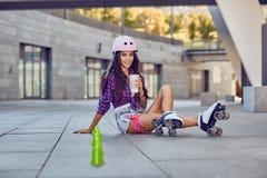 Chica joven feliz que goza de patinaje sobre ruedas con café Imagen de archivo