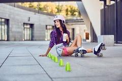Chica joven feliz que goza de patinaje sobre ruedas con café Imagen de archivo libre de regalías