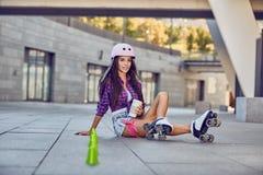 Chica joven feliz que goza de patinaje sobre ruedas con café Fotos de archivo