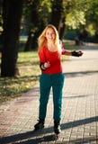 Chica joven feliz que goza de patinaje sobre ruedas en parque Imagenes de archivo