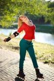 Chica joven feliz que goza de patinaje sobre ruedas en parque Imagen de archivo libre de regalías