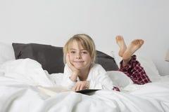 Chica joven feliz que lee un libro Imagen de archivo libre de regalías
