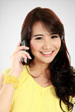 Chica joven feliz que llama por el teléfono Imágenes de archivo libres de regalías