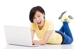 Chica joven feliz que miente en el piso con un ordenador portátil Fotos de archivo libres de regalías