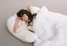 Chica joven feliz que miente en la almohada Fotos de archivo