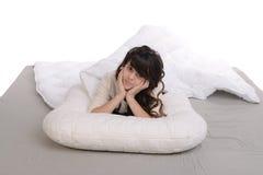 Chica joven feliz que miente en la almohada Imagen de archivo libre de regalías