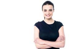 Chica joven feliz que presenta, brazos cruzados Imágenes de archivo libres de regalías