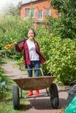 Chica joven feliz que presenta con la carretilla y la pala en jardín en Fotografía de archivo