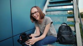 Chica joven feliz que ríe mientras que se sienta en las escaleras que experimentan la tecnología de la realidad virtual La mujer  almacen de video