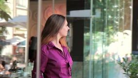 Chica joven feliz que sale de un café en la calle almacen de metraje de vídeo