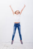 Chica joven feliz que salta en el fondo blanco Fotos de archivo libres de regalías