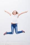 Chica joven feliz que salta en el fondo blanco Foto de archivo