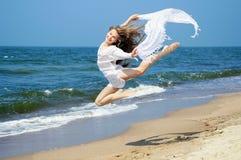 Chica joven feliz que salta en la playa Imagenes de archivo