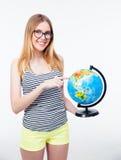 Chica joven feliz que señala el finger en el globo del mundo Imagenes de archivo