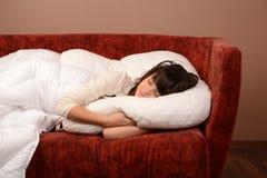 Chica joven feliz que se desliza en el sofá Fotos de archivo libres de regalías