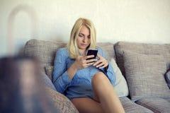 Chica joven feliz que se relaja en el goce del sofá Imagen de archivo