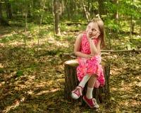 Chica joven feliz que se sienta en el bosque que mira el espacio de la copia Fotos de archivo