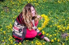 Chica joven feliz que se sienta en el parque en un campo de la hierba y de los dientes de león Foto de archivo