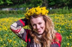 Chica joven feliz que se sienta en el parque en un campo de la hierba y de los dientes de león Foto de archivo libre de regalías