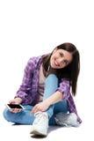 Chica joven feliz que se sienta en el piso con smartphone Foto de archivo