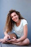 Chica joven feliz que se sienta en el piso que escucha la música Fotografía de archivo