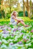 Chica joven feliz que se sienta en la hierba Fotografía de archivo libre de regalías
