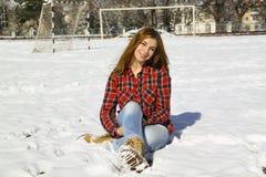 Chica joven feliz que se sienta en la nieve en el parque Fotografía de archivo