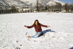 Chica joven feliz que se sienta en la nieve en el parque Imagen de archivo libre de regalías