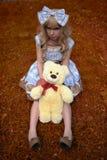 Chica joven feliz que se sienta en prado con el oso de peluche en verano vestido como muñeca Imagen de archivo libre de regalías