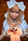 Chica joven feliz que se sienta en prado con el oso de peluche en verano vestido como muñeca Imagen de archivo