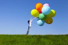 Chica joven feliz que sostiene el manojo de globos fotos de archivo libres de regalías