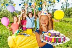 Chica joven feliz que sostiene la torta de cumpleaños con la vela Imagenes de archivo