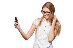 Chica joven feliz que toma el selfie con el teléfono celular, en vidrios, sobre el fondo blanco Imagen de archivo