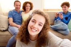 Chica joven feliz que toma el selfie con los padres en el fondo Imagenes de archivo