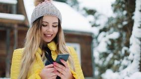 Chica joven feliz que usa el app en smartphone, sonriendo y mandando un SMS en el teléfono móvil Mujer que lleva un abrigo de inv almacen de metraje de vídeo