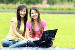 Chica joven feliz que usa el ordenador portátil al aire libre Imagenes de archivo