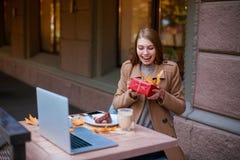 Chica joven feliz, sentándose en un café, sonriendo y sosteniendo una caja de regalo afuera En el otoño imagenes de archivo