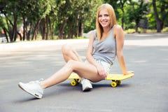 Chica joven feliz siiting en el monopatín Imágenes de archivo libres de regalías