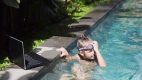 Chica joven feliz y usar un ordenador portátil en la piscina metrajes