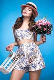 Chica joven fresca en el vestido del verano, sonrisa, estilo retro del perno-para arriba del sombrero con la cesta de flores Cara Fotos de archivo