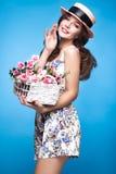 Chica joven fresca en el vestido del verano, sonrisa, estilo retro del perno-para arriba del sombrero con la cesta de flores Cara Fotos de archivo libres de regalías