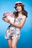 Chica joven fresca en el vestido del verano, sonrisa, estilo retro del perno-para arriba del sombrero con la cesta de flores Cara Imagenes de archivo