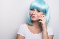 Chica joven fresca en estilo futurista moderno con la peluca azul que presenta sobre blanco Fotos de archivo libres de regalías