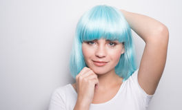 Chica joven fresca en estilo futurista moderno con la peluca azul que presenta sobre blanco Fotos de archivo