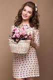 Chica joven fresca, vestido de seda ligero, sonrisa, estilo retro del perno-para arriba de los rizos con la cesta de flores Cara  Imagen de archivo libre de regalías