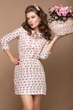 Chica joven fresca, vestido de seda ligero, sonrisa, estilo retro del perno-para arriba de los rizos con la cesta de flores Cara  Imagenes de archivo