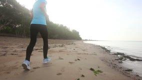 Chica joven funcionada con a lo largo de la playa en la salida del sol almacen de metraje de vídeo