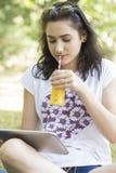 Chica joven hermosa, adolescente, sentándose en la hierba, usando un di Fotos de archivo libres de regalías